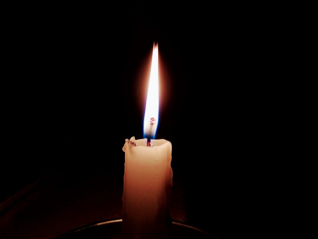 image of a candle lit in the darkness
